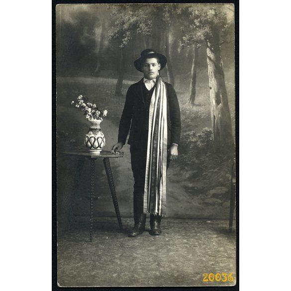Fiú népviseletben, kalapban csizmában, szalaggal, különös háttér, Magyarország, 1920-as évek, Eredeti fotó, papírkép.